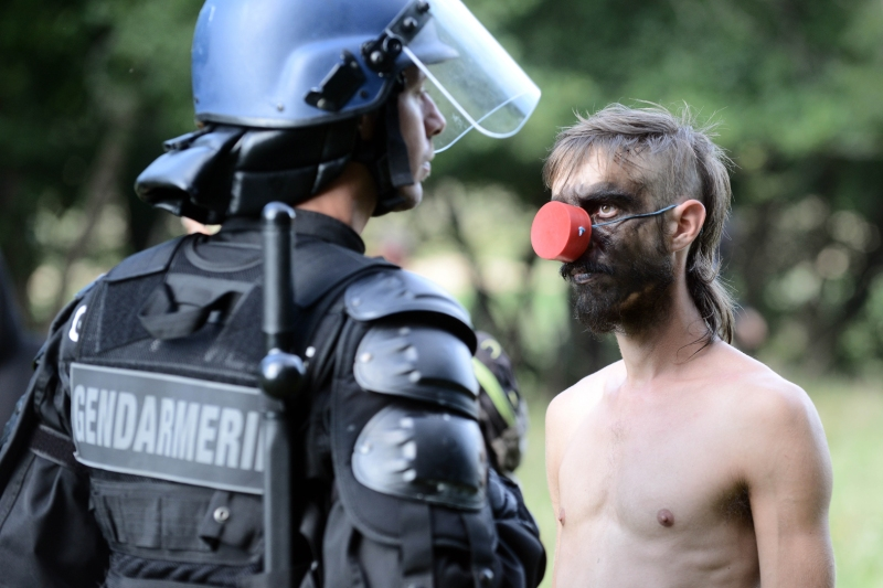 An environmental activist confronts a riot policeman securing a construction site in the Sivens forest, as clearing has started in preparation of the Sivens dam construction, on September 9, 2014 near Gaillac, in the Tarn region. Although the construction of the dam would help supply water to nearby farms, it would remove a 13 hectares long reservoir of biodiversity. Proponents of the dam - including the FDSEA (Departemental Federation of syndicated farmers) - deemed necessary to secure water supplies for farmers. Opponents - backed by French Europe Ecologie Les Verts (EELV) green party member of the European Parliament - are moved by the disappearance of a wetland sheltering 94 protected species and therefore denounce the projected irrigated agricultural model. AFP PHOTO / REMY GABALDA